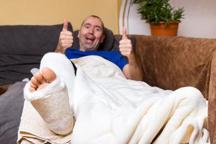 Mann liegt mit einem Gipsbein auf dem Sofa
